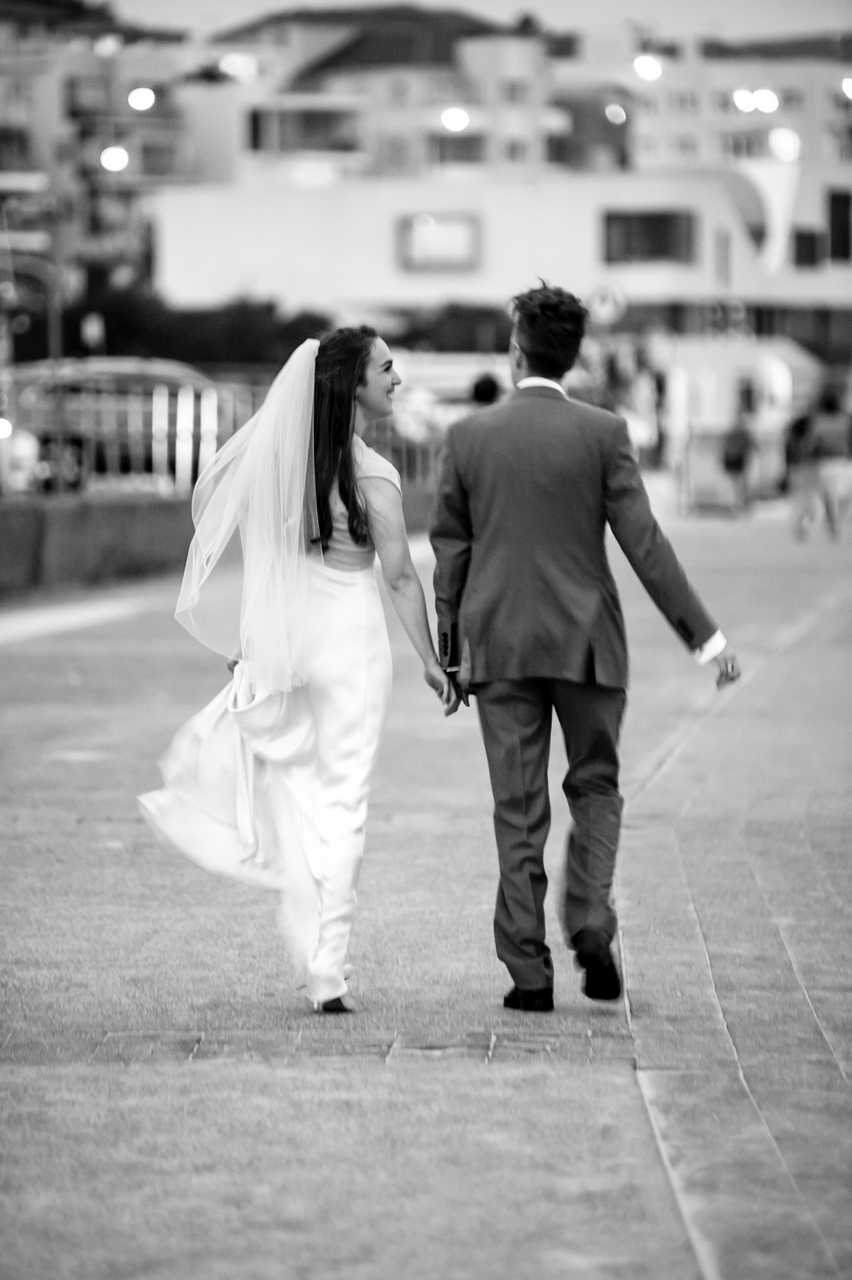 black and white photo of the couple walking down the promenade at bondi beach