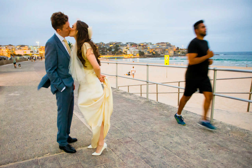 couple kiss at bondi beach while jogger goes by