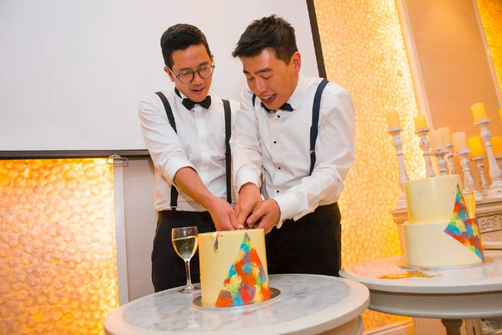 just married 2 grooms cutting wedding cake